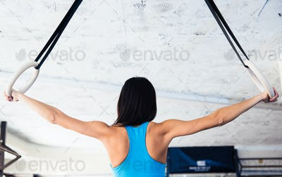 Back view portrait of woman working out on gimnastic rings