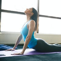 Young fit woman stretching on yoga mat