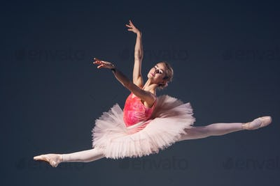 Beautiful female ballet dancer on a grey background.