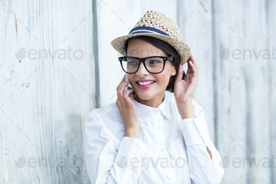 Pretty brunette on the phone in front of wooden grey planks