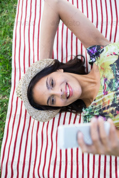 Smiling beautiful brunette lying on the blanket and using her phone