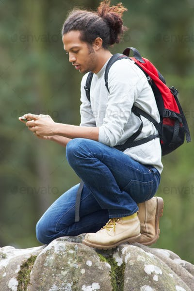 Man Using Mobile Phone Whilst Hiking In Countryside