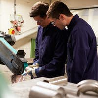 Engineer Teaching Apprentice To Use Grinding Machine