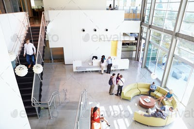 Reception Area Of Modern Office Building With People