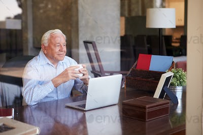 View Of Senior Man Using Laptop Through Window