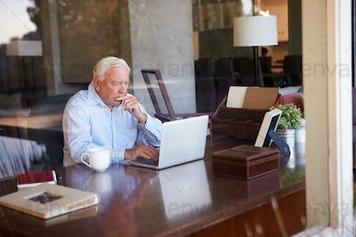 View Of Senior Man Using Laptop Through Window