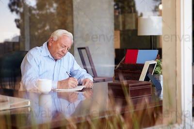 Senior Man Writing Memoirs In Book Sitting At Desk