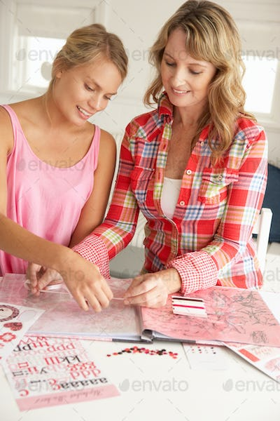 Mother and teenage daughter scrapbooking