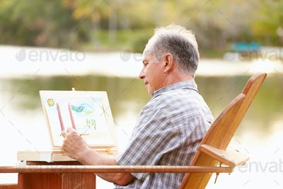Senior Man Sitting At Outdoor Table Painting Landscape