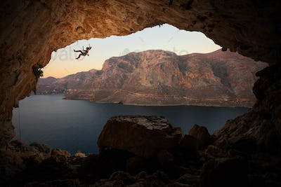 Female rock climber falling of cliff in big cave
