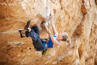 Rock climber struggling to make next movement up
