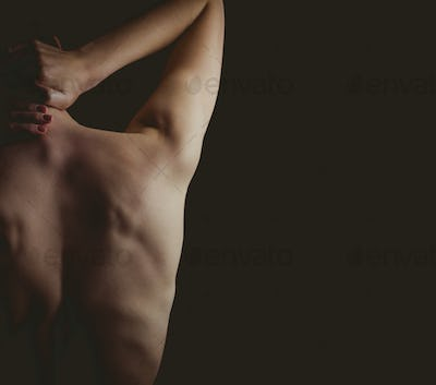 Nude woman with a neck injury on black background
