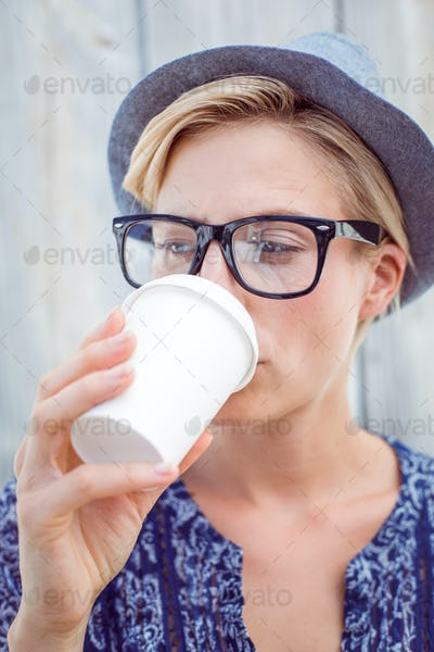 Pretty blonde woman drinking coffee on wooden background