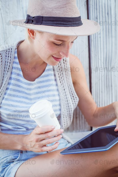 Pretty blonde woman using her tablet and holding goblet on wooden background