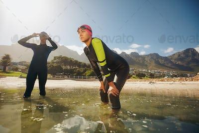 Determined athletes in wet suits preparing for triathlon