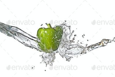 fresh water splash on green sweet pepper isolated on white