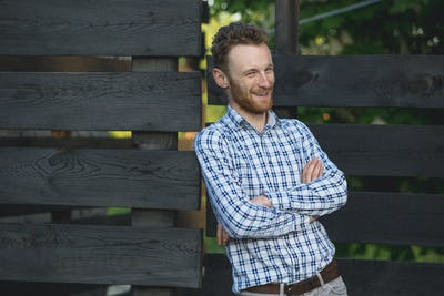 Portrait of young fashionable man against wooden fence