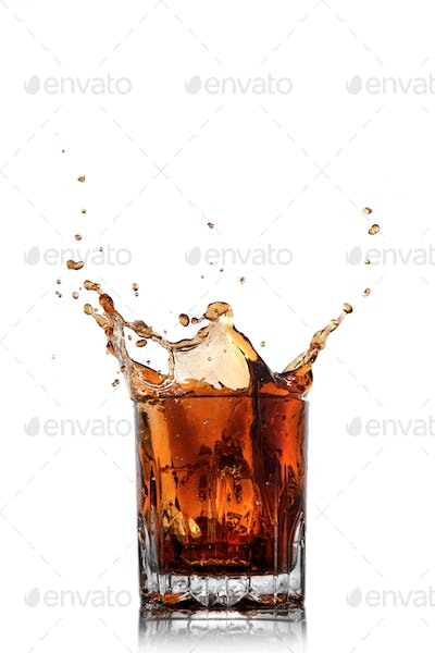 splash of cola in glass isolated on white
