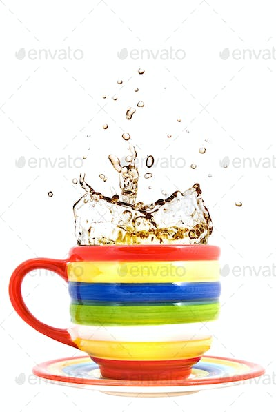 color cup and splash of tea isolated on white