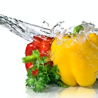 red, yellow, green pepper and parsley with water splash isolated