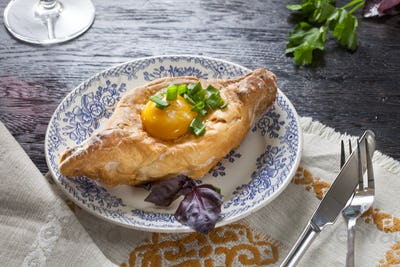 Khachapuri on plate with herbs