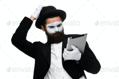 Man with a face mime working on laptop