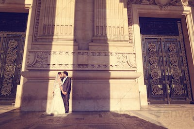Bride and groom in front of a big building