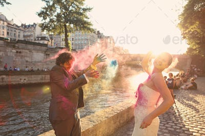 Bride and groom having fun in the sunlight with holi powder