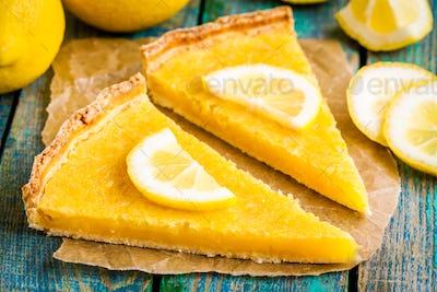 two pieces of lemon tart with slice of lemons closeup