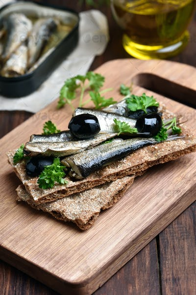 Sprats, herbs and olives on bread