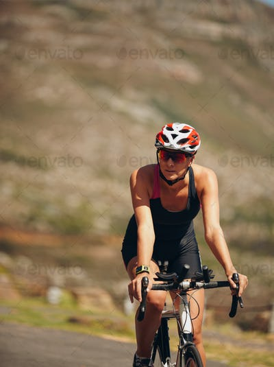 Woman cycling on countryside road