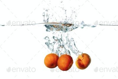 Fresh tangerine fruits falling in water splash