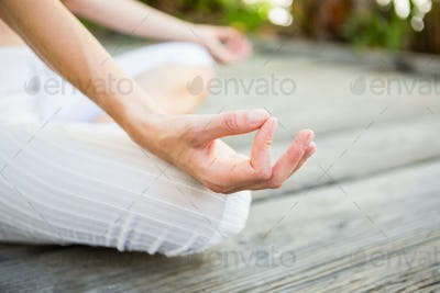 Fit woman meditating outside on a sunny day