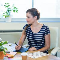 Smiling casual businesswoman working on digitizer in the office