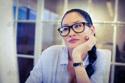 Bored woman sitting at her desk in creative office