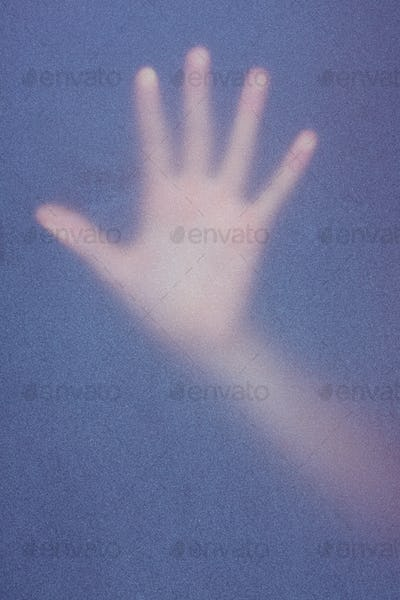 Hand touching frosted glass in the shadow
