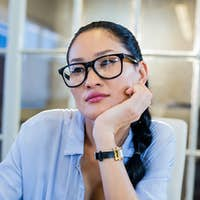 Thoughtful businesswoman sitting at her desk in the office