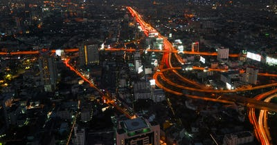 Futuristic night cityscape with traffic across street. Bangkok, Thailand