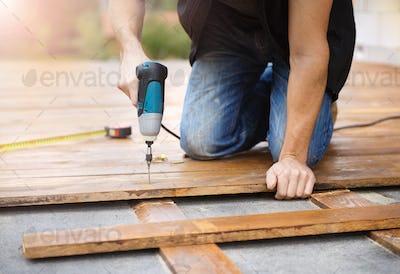 Handyman installing wooden flooring