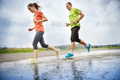 Couple running in rainy weather