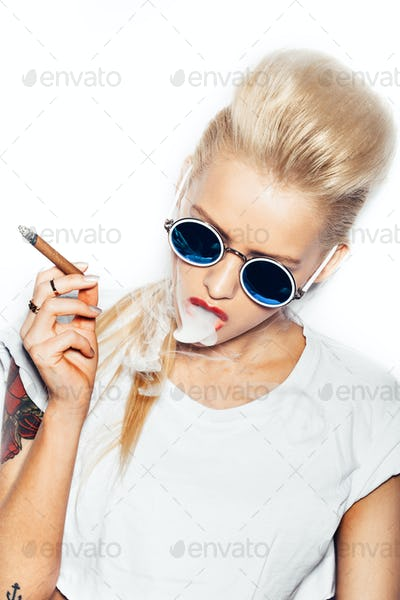 Sexy blonde woman in sunglasses smoking cigar