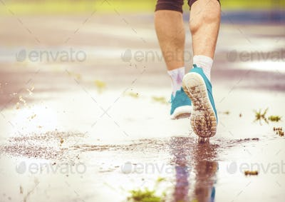 Young man running in rainy weather