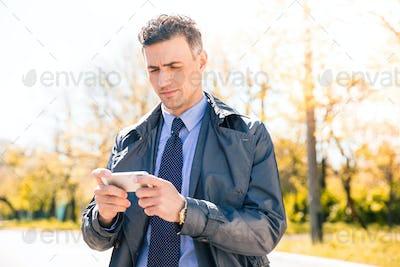 Confident businessman using smartphone