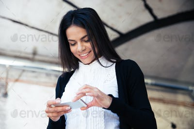 Happy businesswoman using smartphone in cafe
