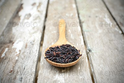 Close up of riceberry in spoon on old wooden