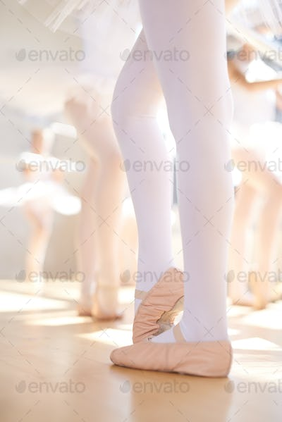 Young ballerina wearing pointe shoes in class