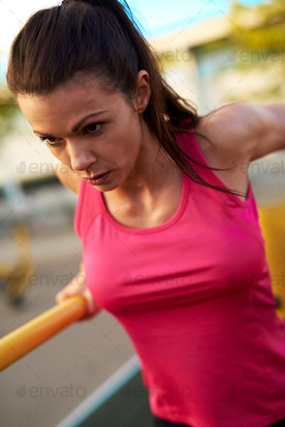Close up of woman concentrating while doing tricep dips.