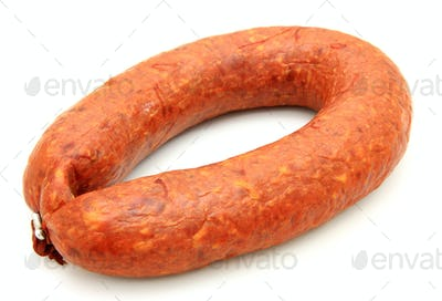 Tasty sausage is curtailed by a ring lies on a white background