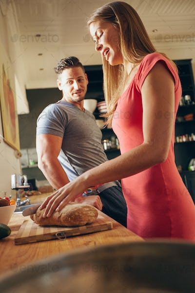 Young couple in kitchen preparing food