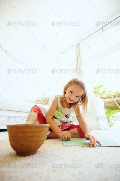 Young girl sitting on the floor drawing